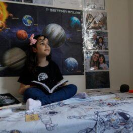 Nicole Oliveira, cea mai tânără astronomă din lume, în camera ei. Stă pe pat, are o carte în mână, în spate are poster cu planete