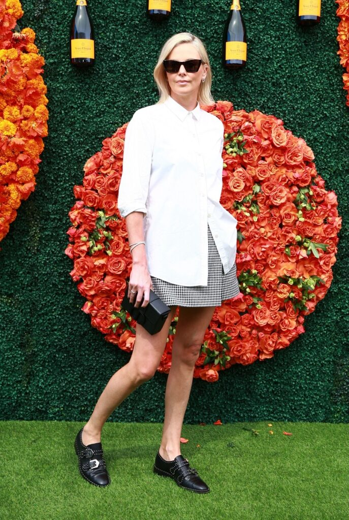Charlize Theron, la evenimentul Veuve Clicquot Polo Classic, din California, din 2021. Charlize Theron a uimit cu ținuta ei cu alb, fustă scurtă și accesorii negre. Flori portocalii pe fundal