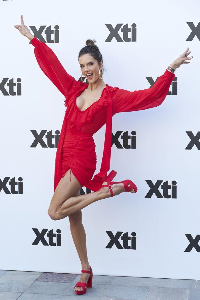 Alessandra Ambrosio într-o rochie roșie în timp ce ridică un picior în sus și mâinile în aer la un show din Madrid din 2018