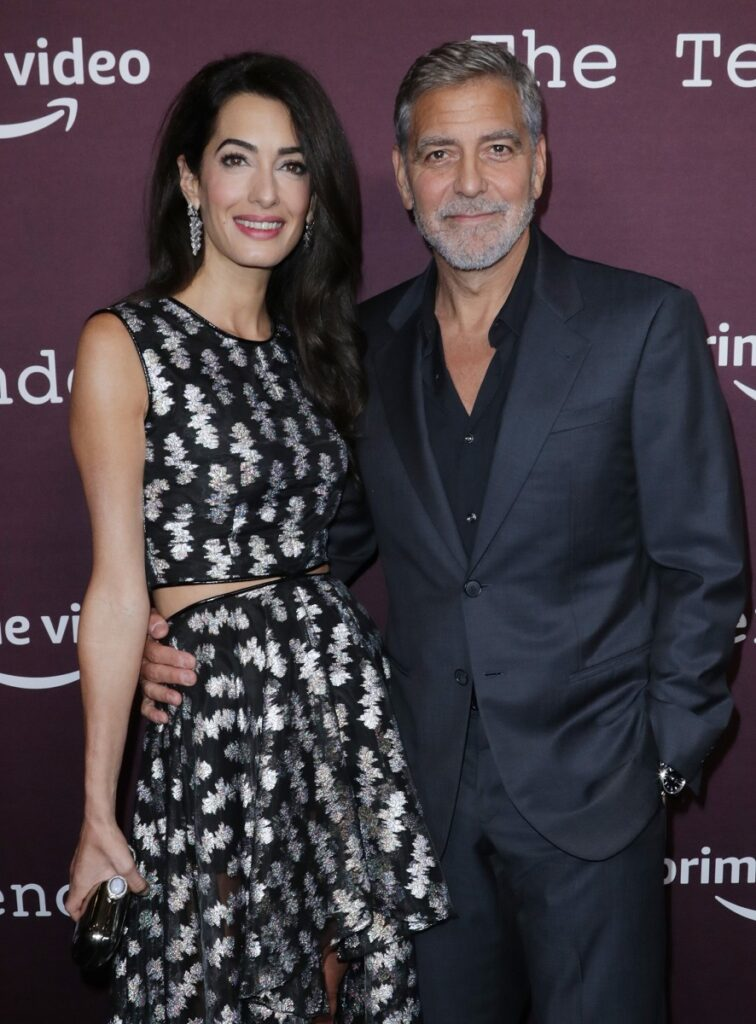 George and Amal Clooney at the premiere of The Tender Bar, October 2021. George wore a black suit, Amal wears a black dress with silver appliqués