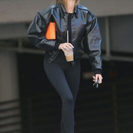Hailey Bieber a făcut o greșeală vestimentară faimoasă, a purtat șosete albe, cu papuci negri. E îmbrăcată în negru, pe stradă, și are o cutie portocalie în mână