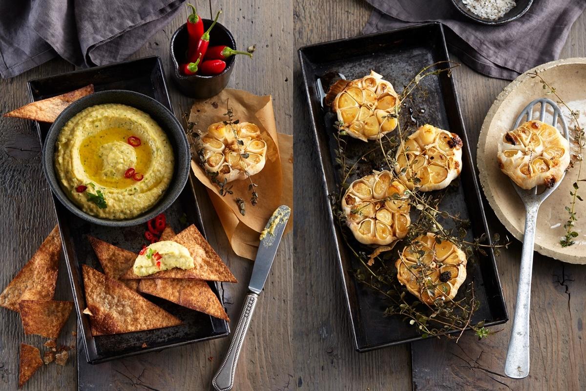 Hummus cu usturoi copt în bol negru, servit cu tortillas și usturoi copt într-o tavă, presărat cu cimbru