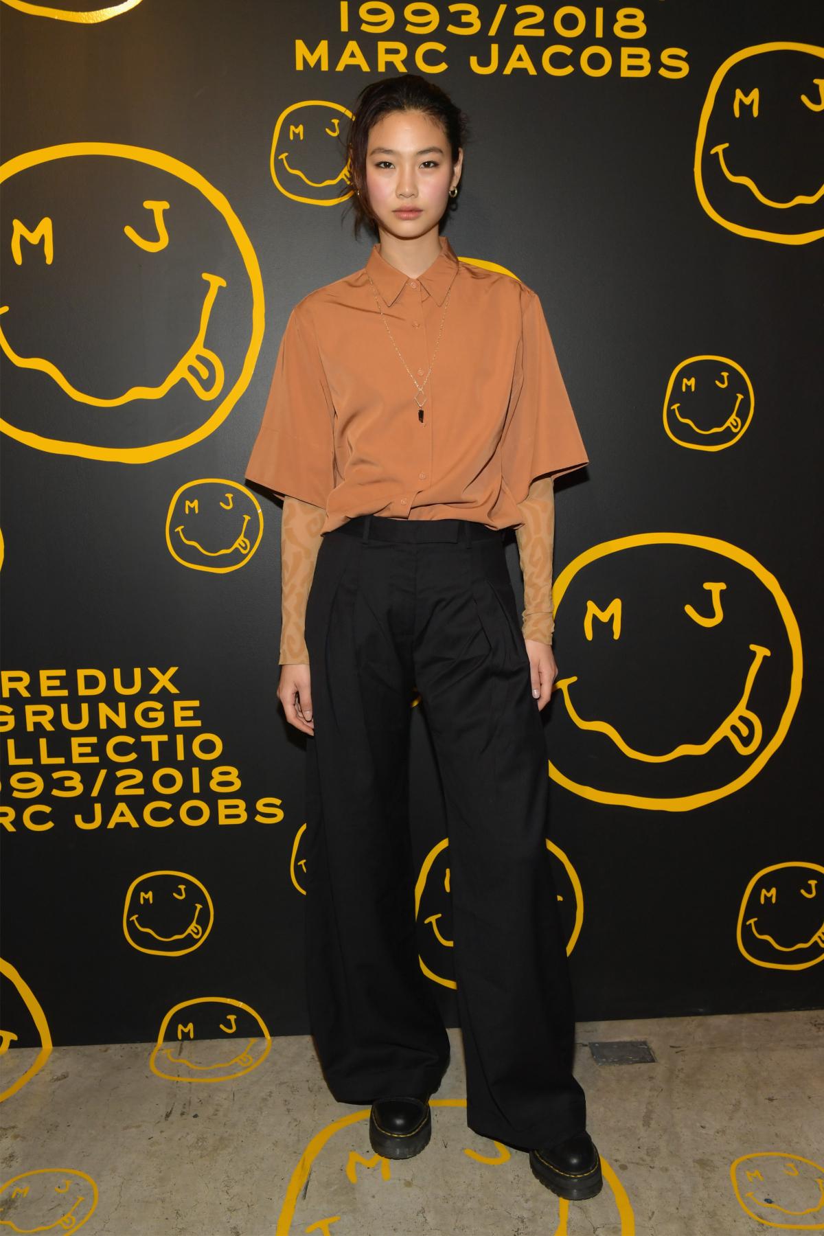 Jung Ho Yeon, îmbrăcată cu un tricou portocaliu și pnataloni largi, negri, la evenimentul The Marc Jacobs Redux Grunge Collection, în 2018