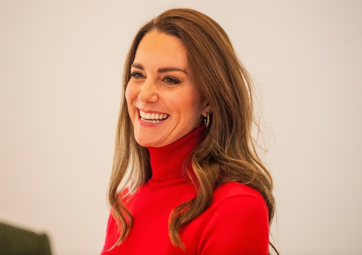 Kate Middleton, fotografie portret, într-o maletă roșie, în timp ce zâmbește