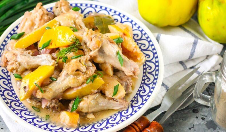 Mâncare de gutui cu pui într-o farfurie, pe un ștergar, alături de tacâmuri și două gutui