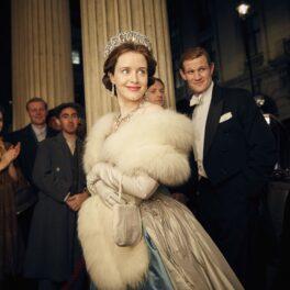 Matt Smith și Claire Foy i-au jucat e Prințul Philip și Regina Elisabeta în primele două sezoane ale serialului The Crown. Ea poartă o rochie albastră, cu o jachetă de blană albă și are coroana pe cap. Matt Smith e îmbrăcat într-un costum negru, în spatele ei