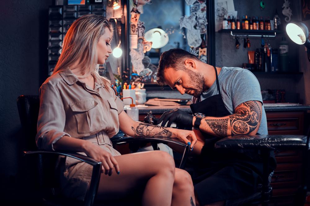 O femeie care își face un tatuaj pe braț, la salon