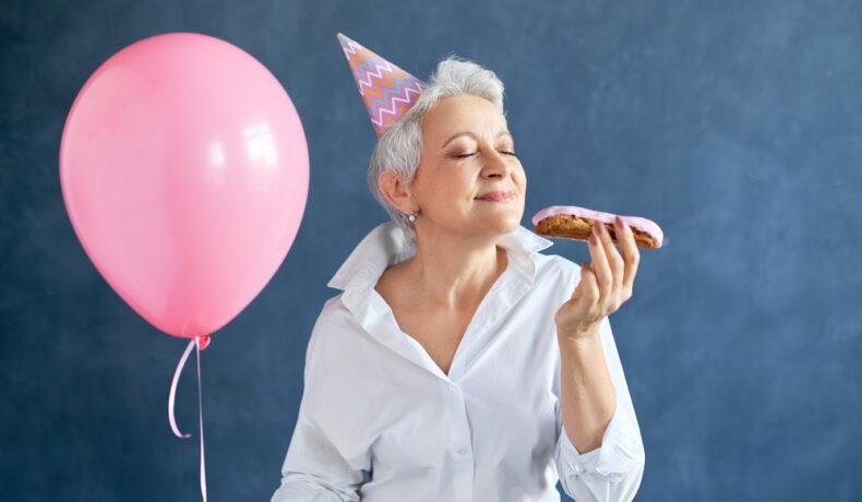 O femeie după 50 de ani care mănâncă un ecler în timp ce sărbătorește ceva