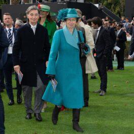 Prințesa Anne, la Prix Qatar Arc de Triomphe, în 2021, Paris. A purtat o haină turcoaz, cu o pălărie în ton. Pe fundal e verdeață, cu bărbați îmbrăcați în negru