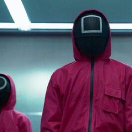 Oameni în costum roșu cu mască pe față reprezentând personajele din Squid Game