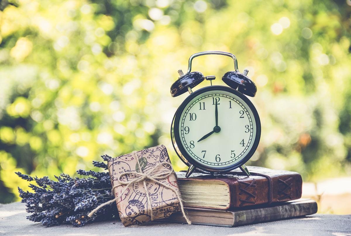 Semnificația orelor în oglindă pusă în scenă de un ceas metalic vintage care stă așezat pe două cărți vechi alături de un cadou și de un buchet de lavandă