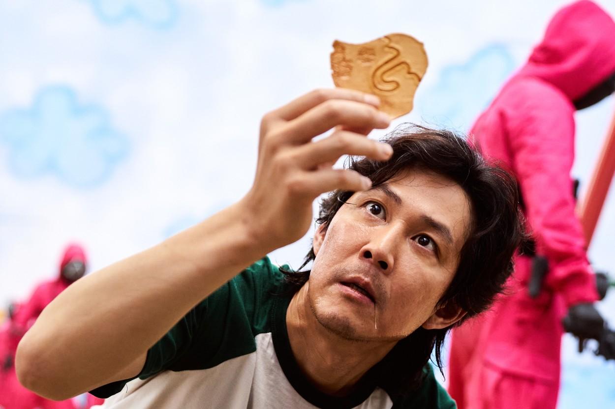 Un personaj din serialul fenomen Squid Game, care ține în mână și analizează un desert dalgona, creat după rețeta dalgona